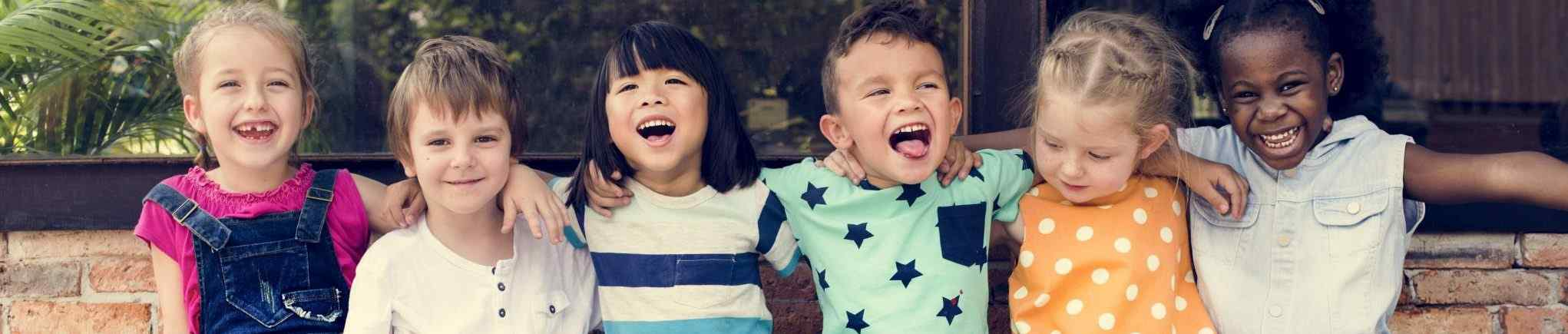 Image of children laughing in a row; courtesy of Shutterstock.